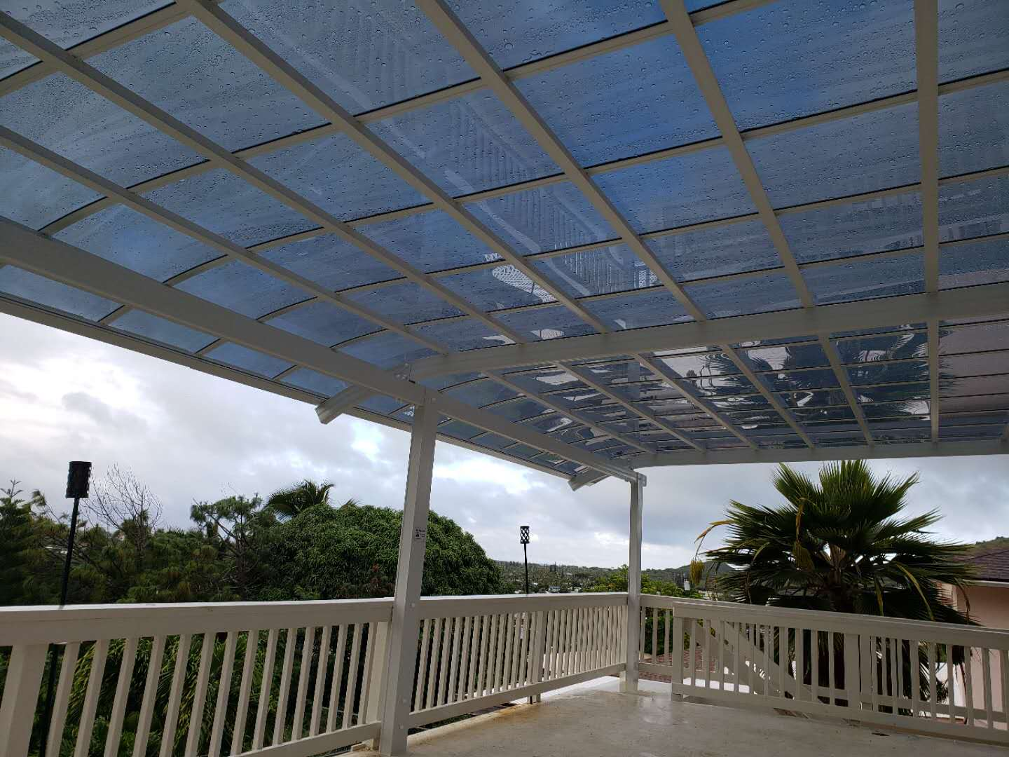 Large patio cover in white frame and dark polycarbonate roof panels